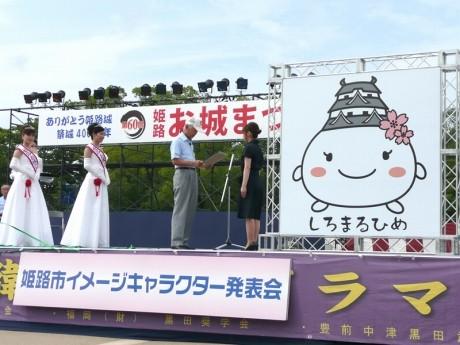 ベストデザイン賞に選ばれ市長から表彰授与される田口さん。