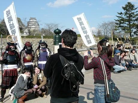 姫路城甲冑隊のメンバーと記念撮影を楽しむ観光者。