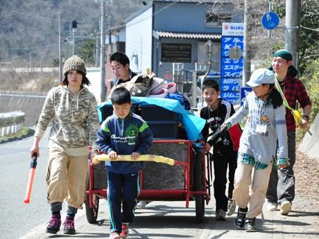 自らの荷物を積むリアカーを引きながら徒歩縦断にチャレンジする参加者の様子。歩行中の安全を確保する同NPO職員ら「サポーター」の姿も見える。