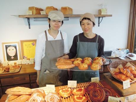 焼き上がったパンを手にほほ笑む北澤慶さん(写真右)砂川典子さん(同左)