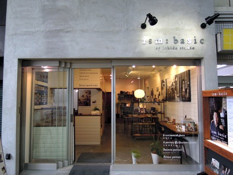 姫路駅前・御幸通商店街の写真館「ism:Basic(イズムベーシック)」。先代社長・石田主計さんの遺影となった肖像写真のポスター(写真右)が店頭を飾る。