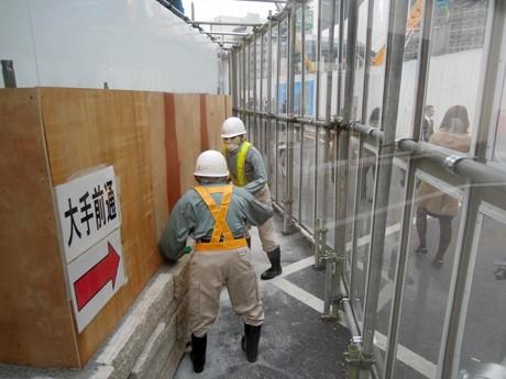 姫路駅前に突然現れたことから謎とされ、駅利用客の間で話題を呼んだ「工事のおっちゃん人形」。正体は、同広場で建設中の施設PRを担う「かかし」。写真は解説パネルの設置前に撮影