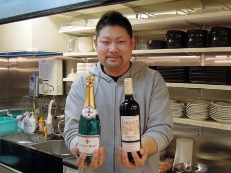 「空け放題」で楽しんでもらう予定のワインとシャンパンを手にする店主の横山亮生さん。姫路・魚町に3月1日オープンする韓国料理店「韓ダイニング Nanami(ナナミ)」(姫路市魚町)で。「空け放題」はオープンを記念し、カウンター上に置いたワインやシャンパンのボトルを無料で楽しんでもらうイベント。2月24日