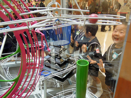4月30日の開業を控えるJR姫路駅の新駅ビル内商業施設「Piole(ピオレ)姫路」(姫路市駅前町)6階に設置されたボールマシンを見る園児たち。26日の除幕式で