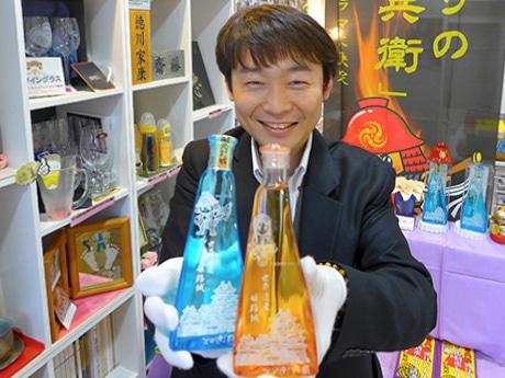 梅酒(写真右)と清酒(同左)のボトルを手にする下林崇史さん。「アニバーサリーギフト」(姫路市本町)で。2月13日