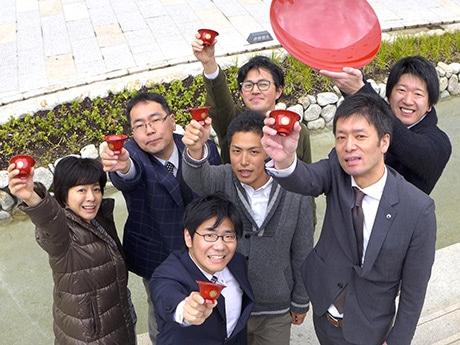 イベントを企画した「官民連携のための 実践型まちづくり人材養成講座」のメンバーら。手にする赤い杯が「官兵衛杯」。JR姫路駅前「キャッスルガーデン」で。2月28日