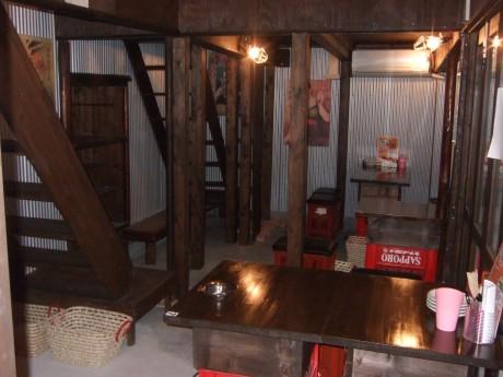 昔ながらの古いイメージを出す壁の塗装や貼り物、ビールや酒の空ケースを利用した机や椅子も手作り。