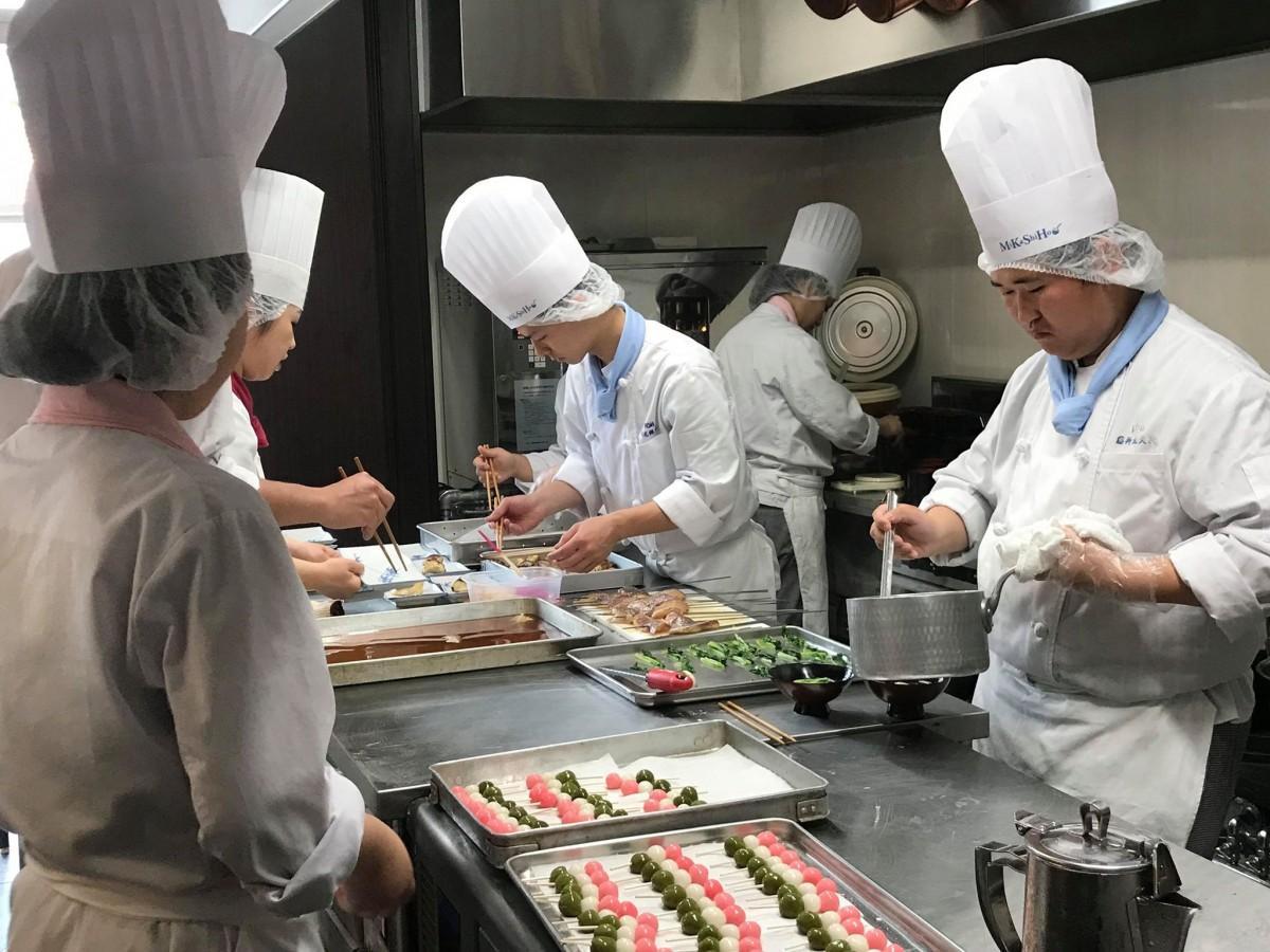 調理・サービスを提供する学生。