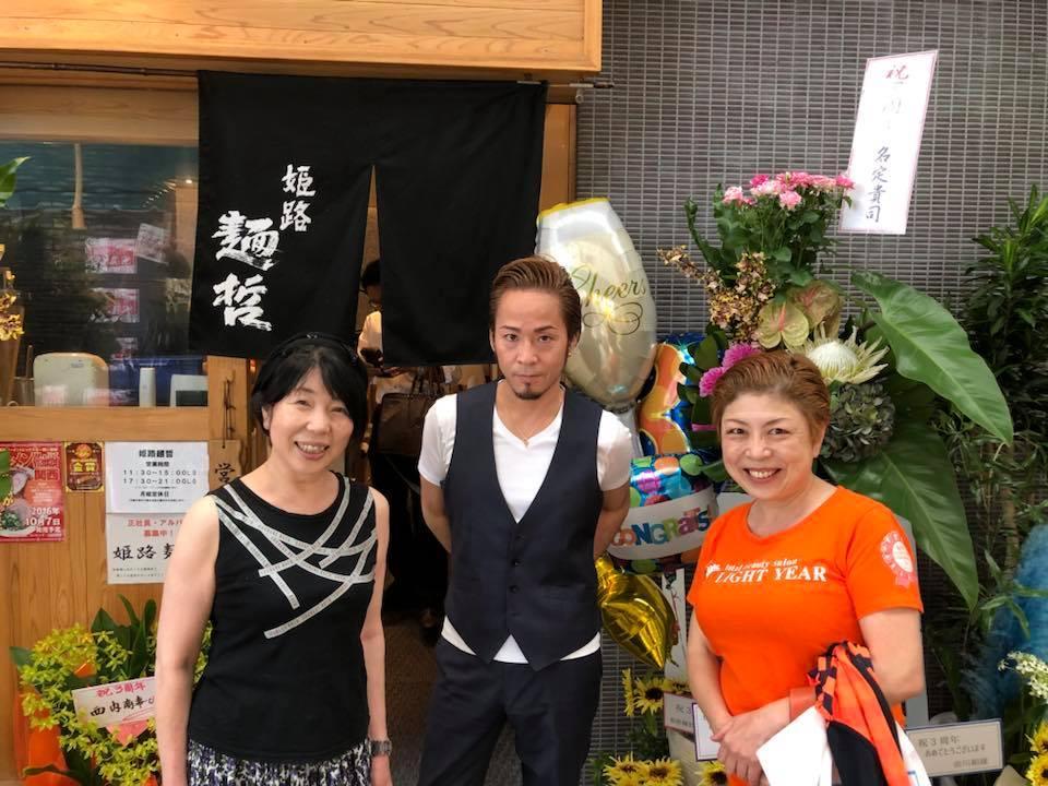 来店客と写真撮影する店主の名定さん(中央)