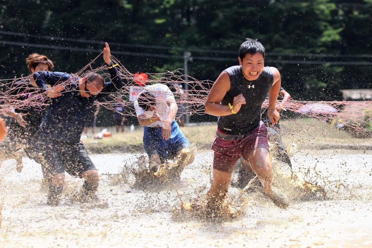 泥にまみれ競技に参加する人たち