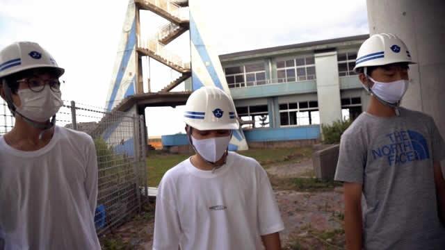 震災遺構 浪江町立請戸小学校跡地にて。長谷川敬人さん(左)