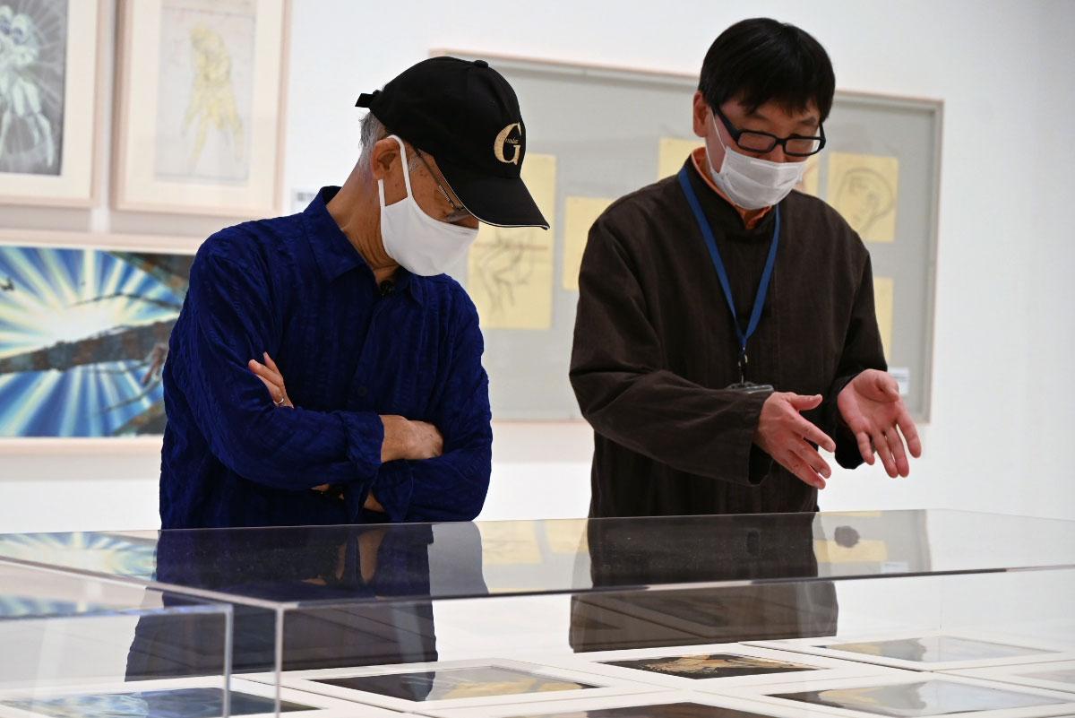 青森県立美術館の工藤健志さん(右)から説明を受ける富野さん