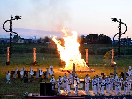 岩木川河川敷に設置されたステージでは伝統舞踊などを披露。竜型の2体の虫人形が奥に見える