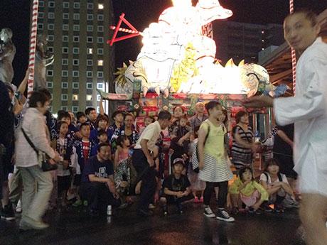 JR弘前駅前にねぷたを展示し、観光客にはんてんをレンタルして記念写真に応じるねぷた団体「必殺ねぷた人」