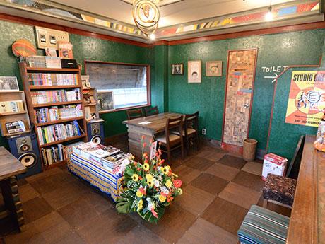カレーライス専門店「CHANTLOOSE(チャントルーズ)」店内。緑を基調とした店内にアナログレコードやビデオテープなどが並ぶ