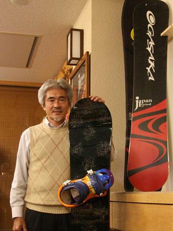 津軽塗スノーボードの生みの親・八木橋綱三さん。脇に抱えるのは、試作品の紋紗(もんしゃ)塗のスノーボード