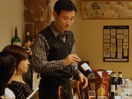 大鰐町出身のソムリエ・阿保孝史さん。手にするのは、最近関心を深めている古代ローマの製法で作られているという蜂蜜入りの甘口赤ワイン
