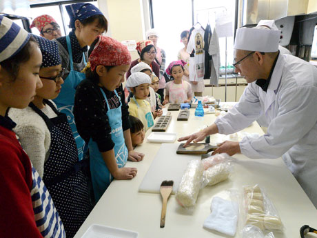 子どもたちに「大王くじ」の作り方を教える佐藤製菓の佐藤力雄さん(右)