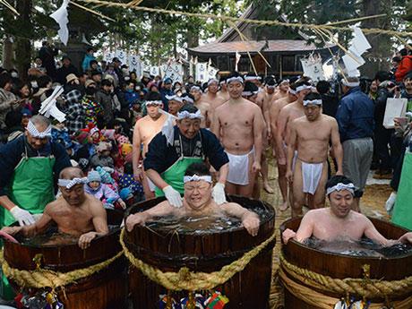 鬼神社の鳥居の前でたるに入った冷水に次々と入っていくふんどし姿の男衆たち
