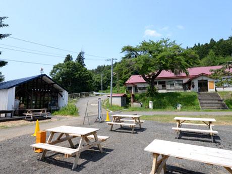 王余魚沢小学校の校庭跡にテーブル席などを設ける「王余魚沢倶楽部」(左の建物)