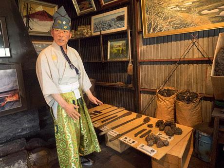 鍛冶場で日本刀の材料となる玉鋼(たまはがね)を説明する刀匠の中畑貢さん