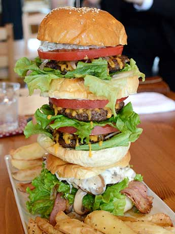 高さ25センチのタワーバーガー。下から「ベーコンモッツァレラバーガー」「ダブルバーガー」「マッシュルームバーガー」「ハンバーガー」が載っている