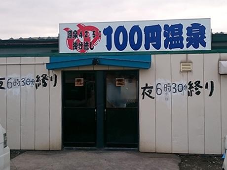 「100円温泉」。田んぼに囲まれたプレハブ小屋