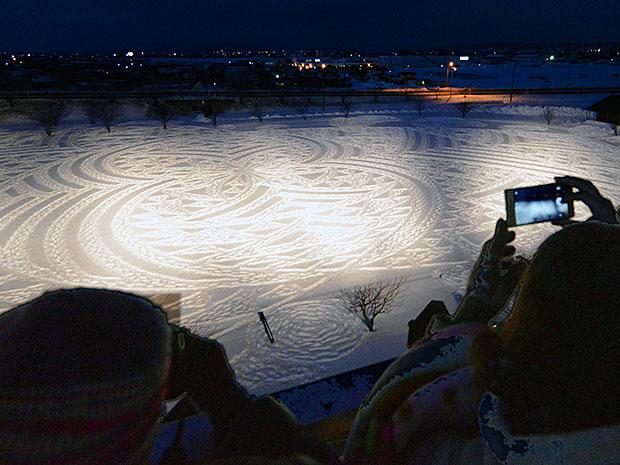 ライトアップされた冬の田んぼアートを見つめる来場者たち