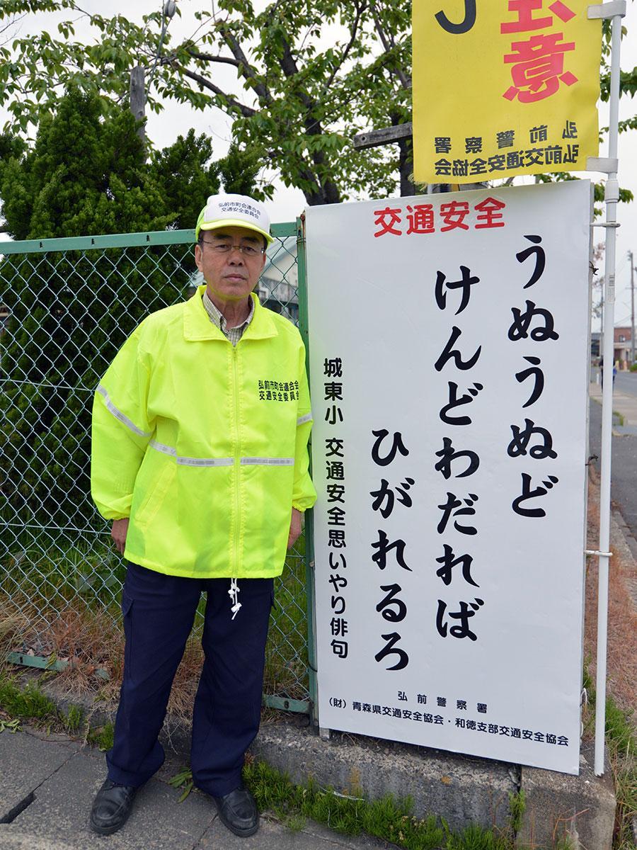 新しくなった看板と青森県交通安全協会・和徳支部交通安全協会の原田利昭さん