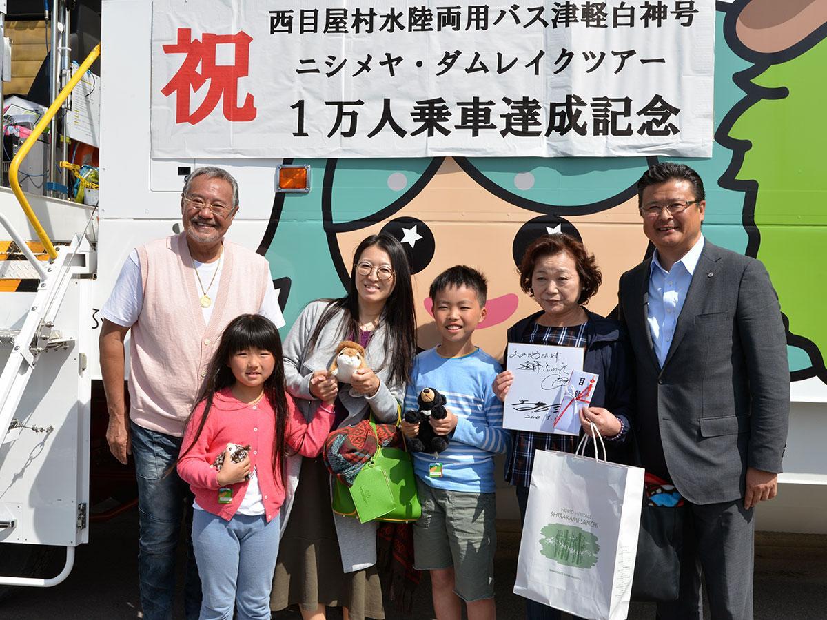 サプライズで登場した吉幾三さん(1番左)と記念撮影する1万人目の乗客とその家族。右端は関和典村長