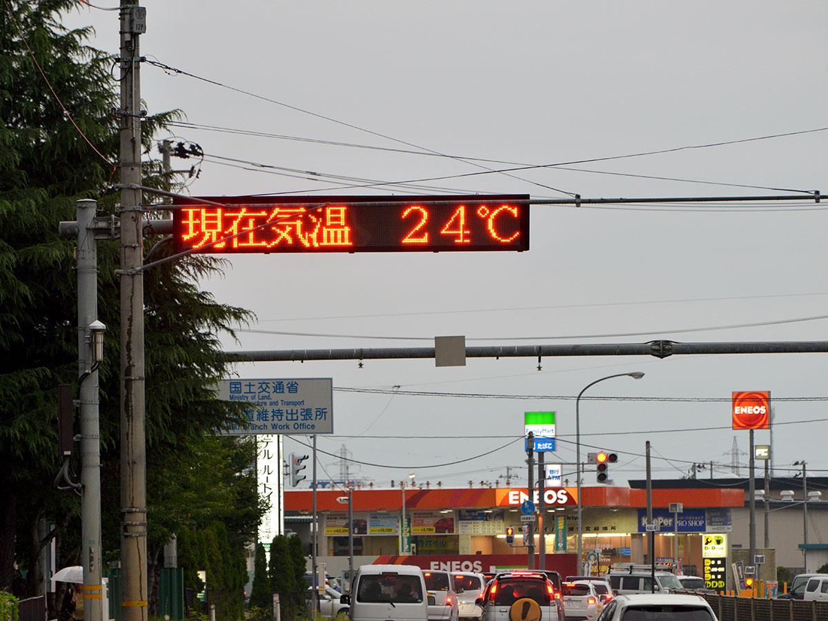気温24度を示す電光掲示板(7月23日、弘前市立東小学校付近の国道7号線で)