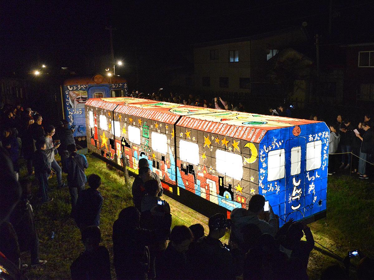 集まった見物客に囲まれた夢のキャンバス号(奥)と慎吾列車ねぷた(手前)(津軽鉄道嘉瀬駅で)