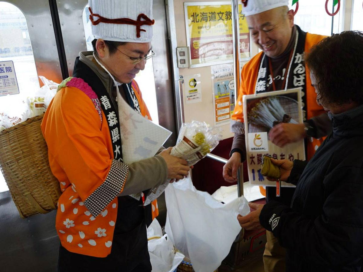 電車内、大鰐温泉もやしの販売員と、購入する乗客
