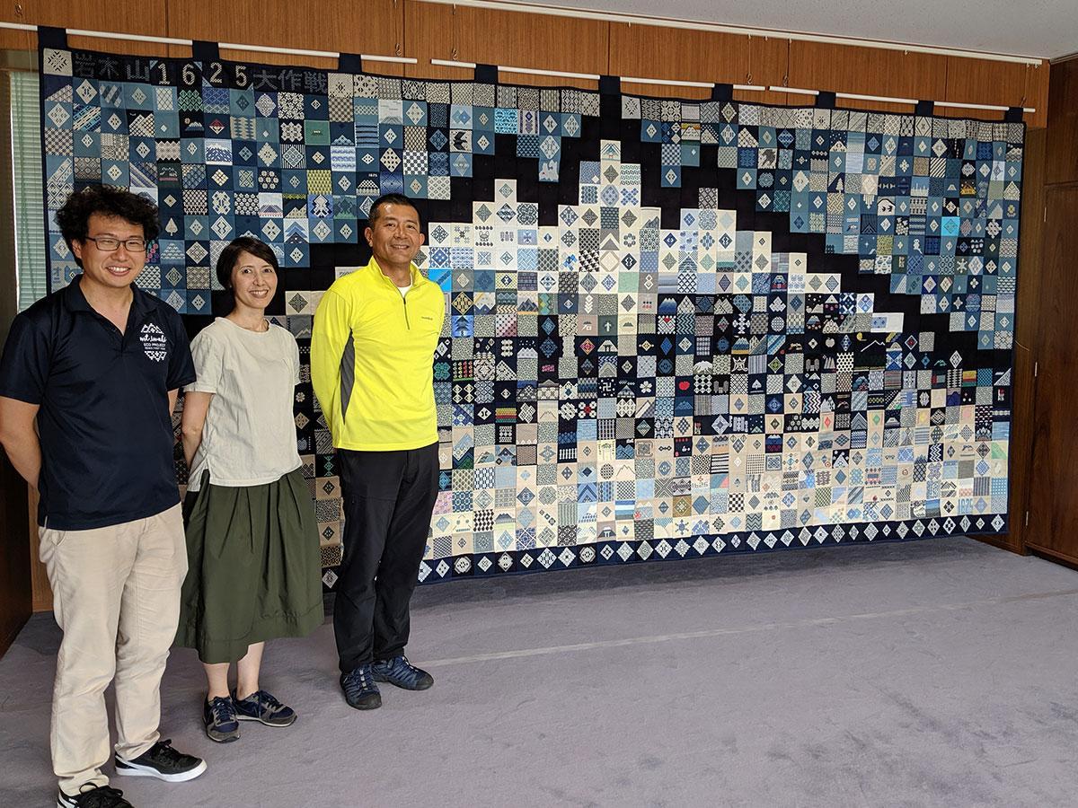 岩木山のタペストリーを背景に並ぶ地域おこし協力隊。左から鎌田祥史さん、佐々木直美さん、伊藤博和さん