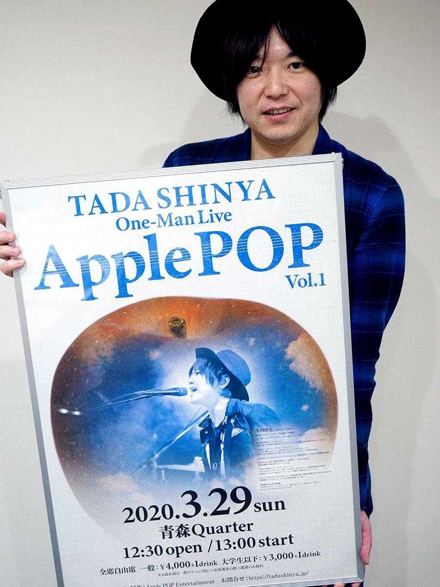 多田慎也さん。ポスターには青空をイメージしたリンゴを描く