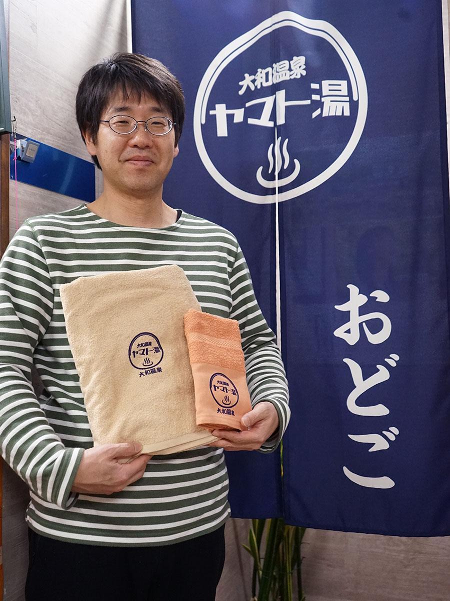 ロゴ入りタオルを手に持つ3代目店主・工藤卓輝さん