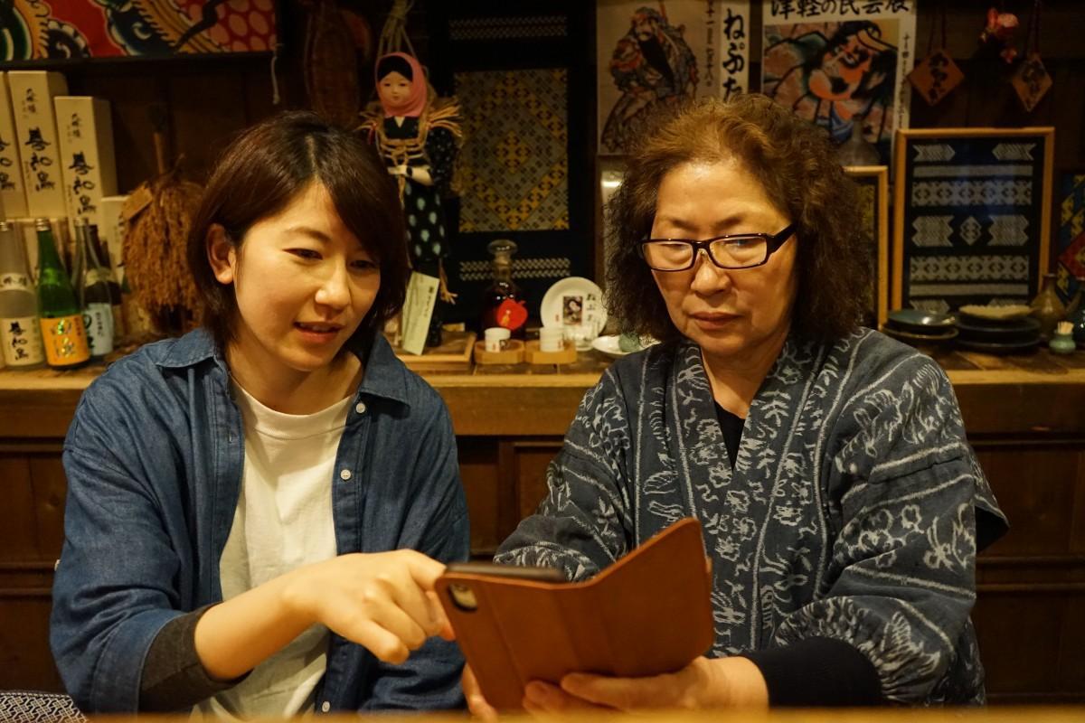 スマートフォンの操作説明をする娘の相馬由貴さん(左)と下山初子さん(右)