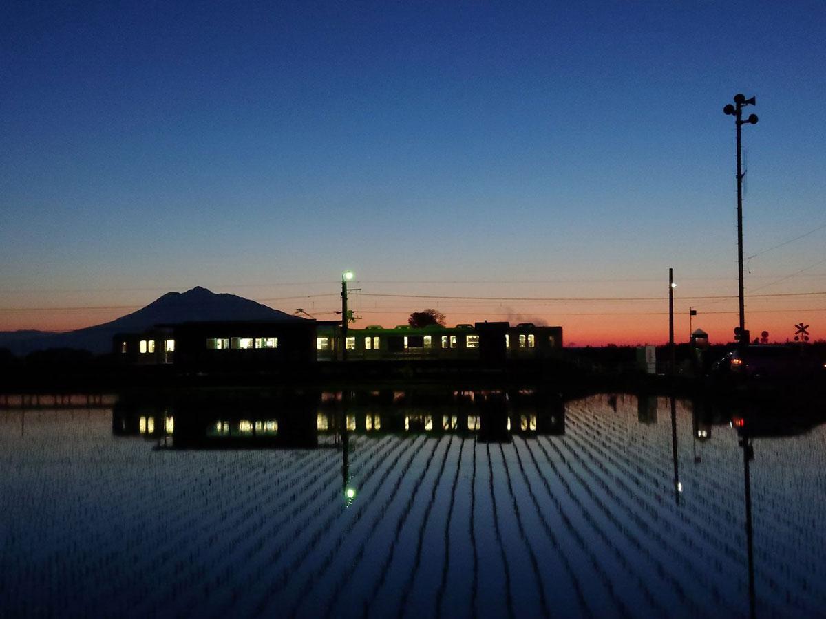 夕日の岩木山を背景に、列車と水田風景が話題を集めた(写真提供:丸目多聞さん)
