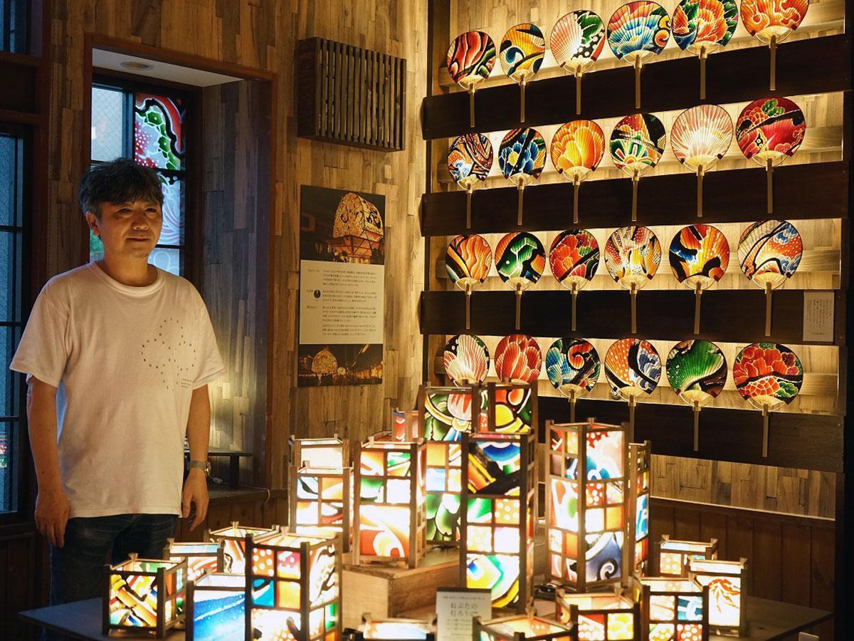 ねぷた絵で作られたうちわや灯篭と店主・木村正幸さん