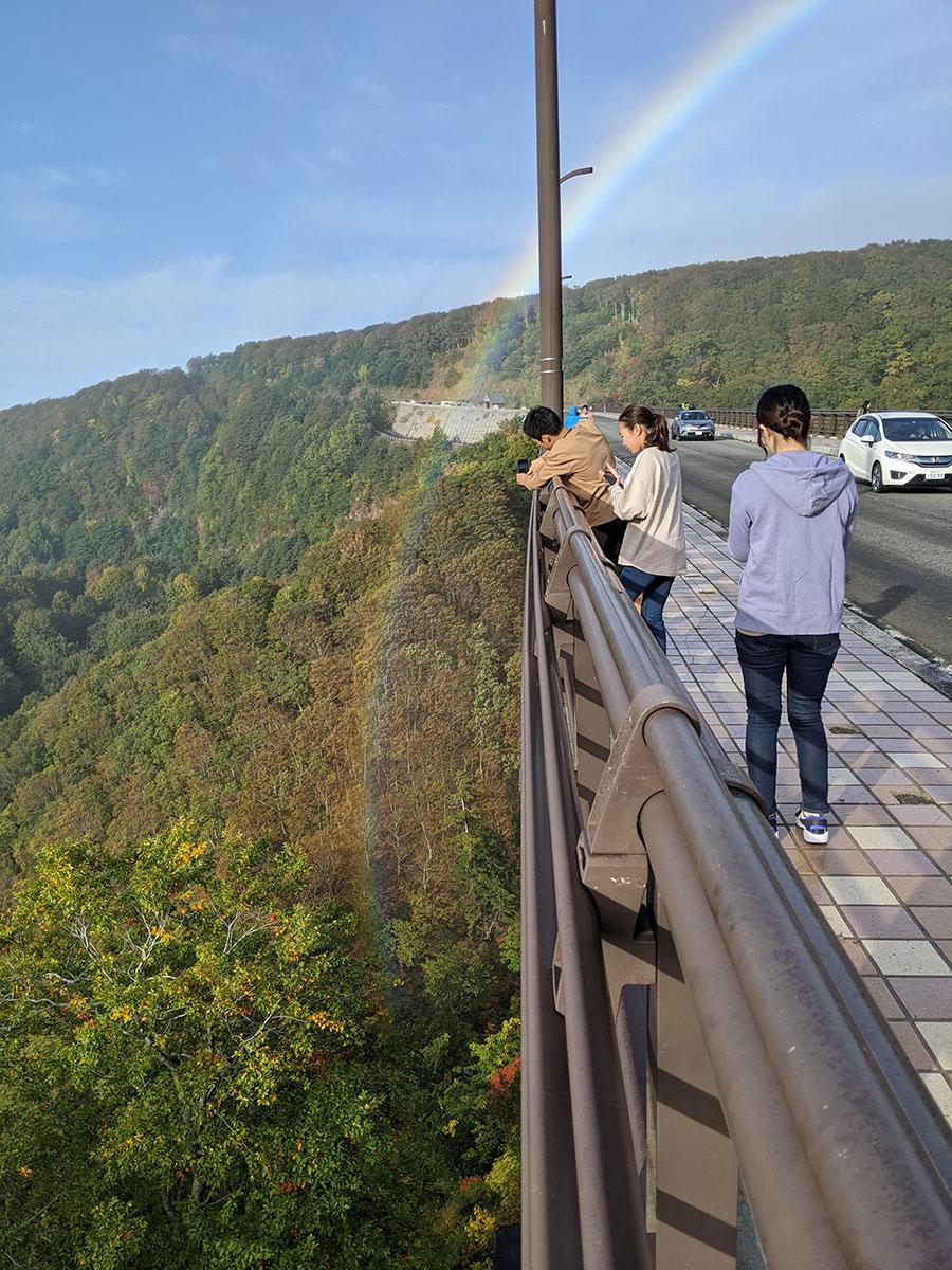 橋の下まで虹がかかり、珍しい景色に写真を撮る見物客が多くいた