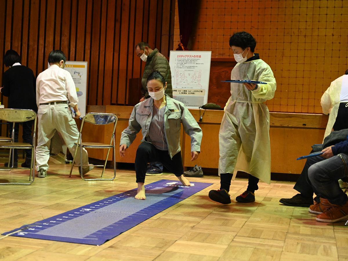 筋力やバランス力をテストする2ステップテストに挑戦する参加者