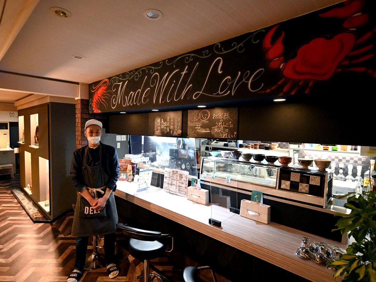 4月1日に1年ぶりに営業を再開した「海の灯」の店主・小友佑介さん。再開にあたりカウンター上に壁画アートを施した
