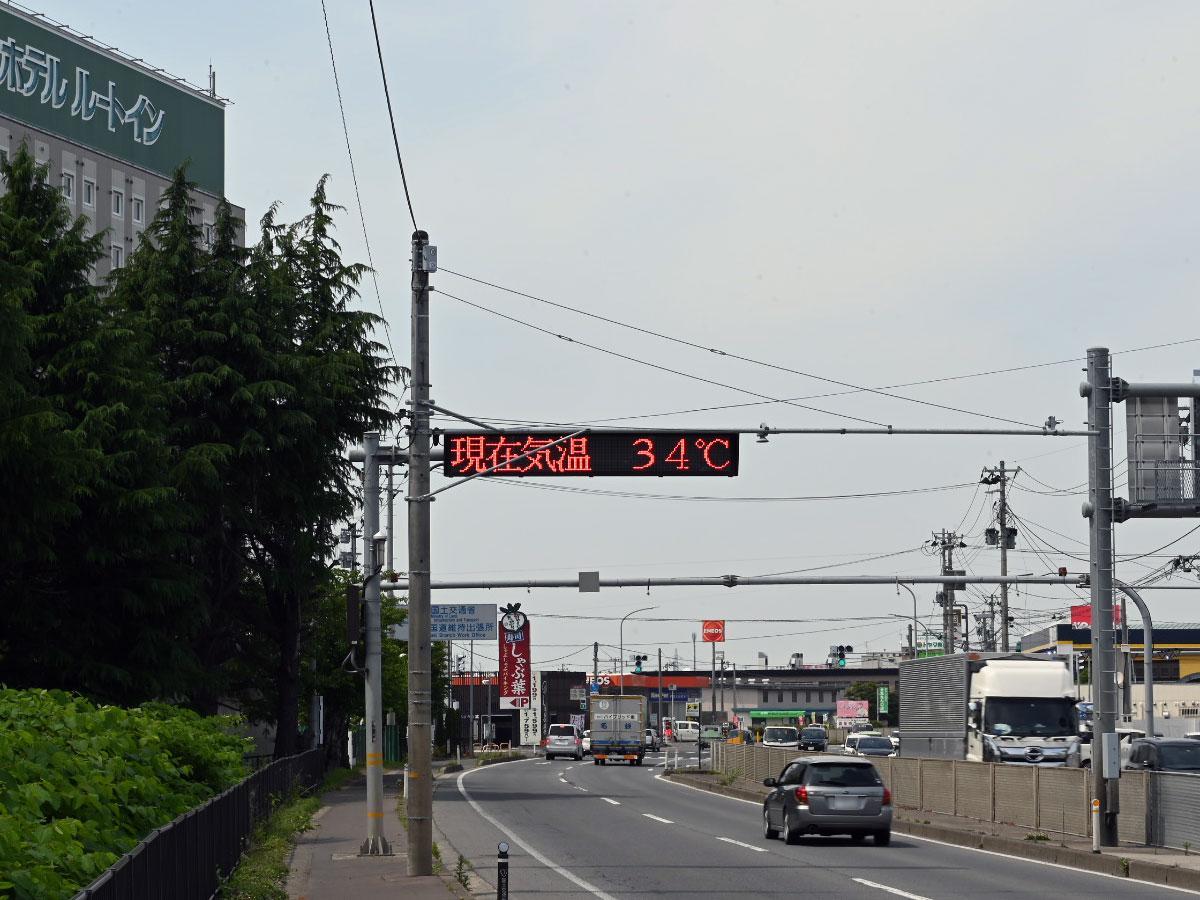 気温34度を表示する電光掲示板の温度計(弘前市立東小学校付近の国道7号線、13時ころ)