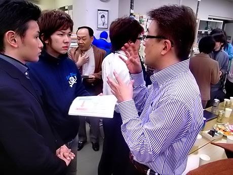 スピーチ後の交流会で名刺交換を行う鎌谷社長と事業プランに対してコメントをもらう参加者。