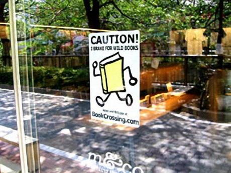 イメージ写真=「COW BOOKS」入り口に貼られたブッククロッシングのラベル。