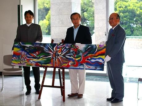 写真=手渡し式の様子。左から、平野理事、秋葉市長、原田館長