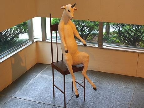 写真=一角獣がいすに腰掛けている作品「繰り返される終わりを待つ」