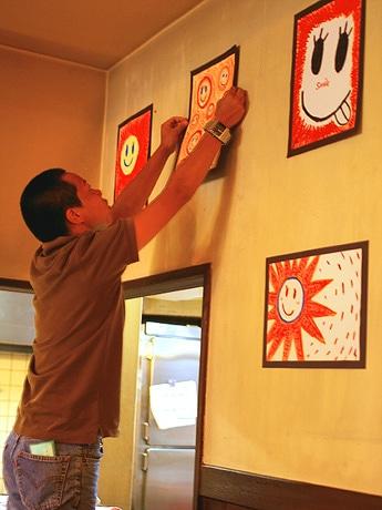 写真=作品を厨房脇の壁面に展示する参加者の山岡新汰さん