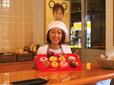 写真=さまざまな種類のドーナツを手に微笑む女性スタッフ