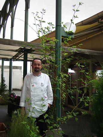 イタリアンレストラン「アレックス」の中庭に生えた約3メートルの「巨大オシロイバナ」と178センチのシェフのブッシ・アレッサンドロさん。